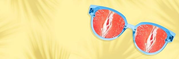 新鮮な景色。サングラス、グレープフルーツをメガネにしたアイウェア、モダンなデザインのチラシ。黄色の背景、コピースペース。夏、パーティー、寒さ、休暇、休息の概念。提案、広告販売のためのチラシ