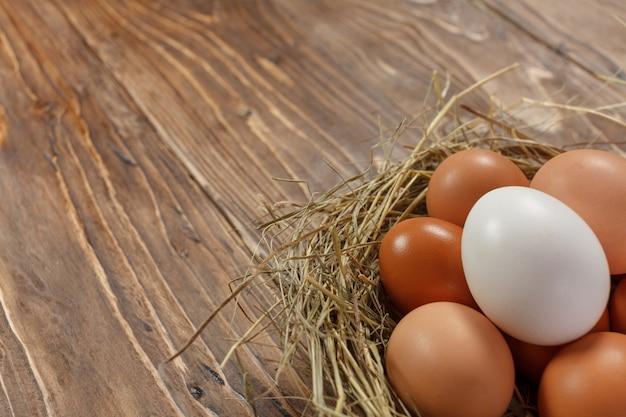 暗い背景の木に新鮮な村の鶏の卵。イースターの側近。バスケットまたはソケット
