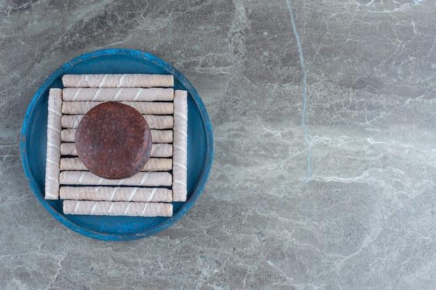 Rotoli di cialda fresca con biscotto al cioccolato su piatto di legno blu.