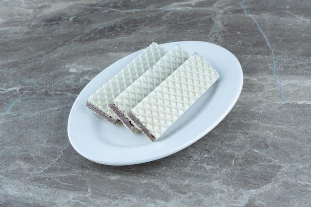Fresh waffle slices on white plate over grey background.