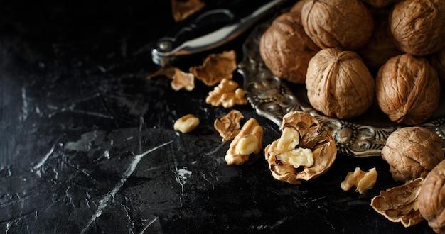 Свежие грецкие орехи с щелкунчиком на темном фоне