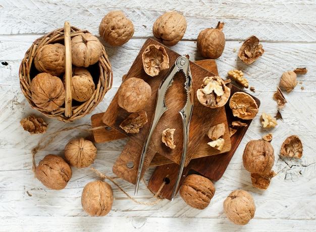 Свежие грецкие орехи с щелкунчиком на старом деревянном столе