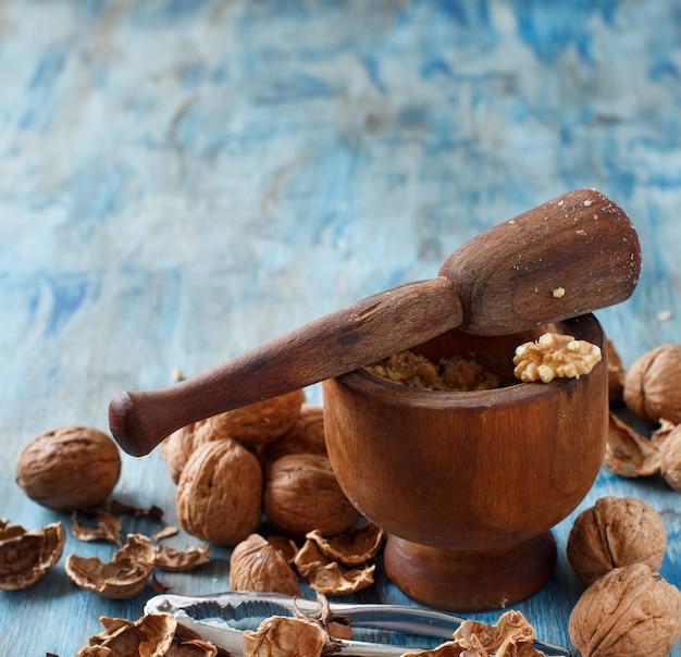 青い木製のテーブルに乳鉢と乳棒で新鮮なクルミをクローズアップ