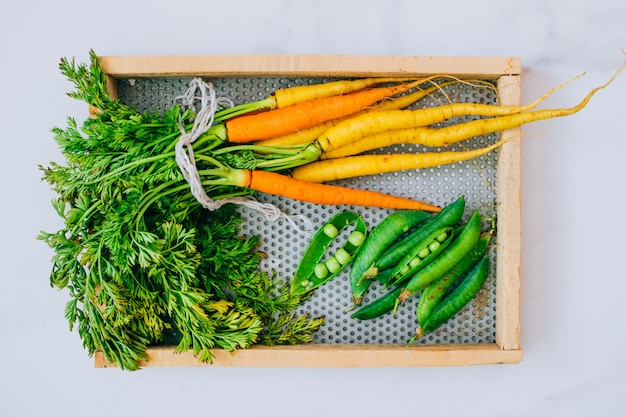 Fresh washed carrots with green peas on wooden tray on a marble background, top view