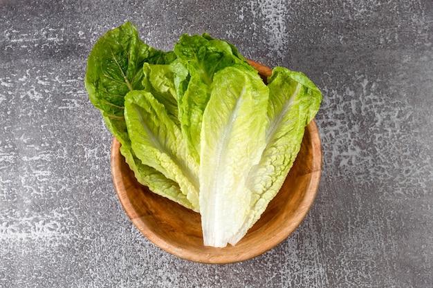 Свежий мытый зеленый салат в деревянной миске, готовый к приготовлению. ингредиенты для приготовления пищи, вегетарианская диета, здоровое питание. вид сверху, место для текста.