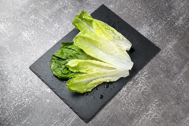 Свежий промытый зеленый салат на черной шиферной разделочной доске, готовой к приготовлению. ингредиенты для приготовления пищи, вегетарианская диета, здоровое питание.