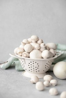 Fresh washed mushrooms in a colander on a white table