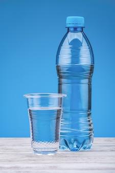 Пресная вода в пластиковой бутылке и стекле на синем фоне. скопируйте пространство.