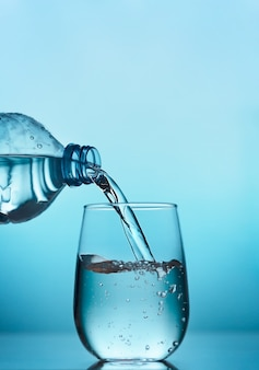 Fresh water pouring from the plastic bottle into a glass on the blue background, vertical orientation