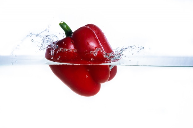 Fresh water splash on red sweet pepper isolated