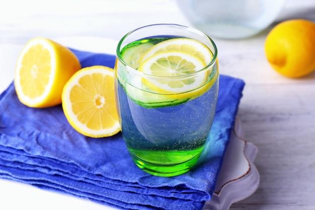 木製のテーブルの上のガラス製品にレモンとキュウリと淡水