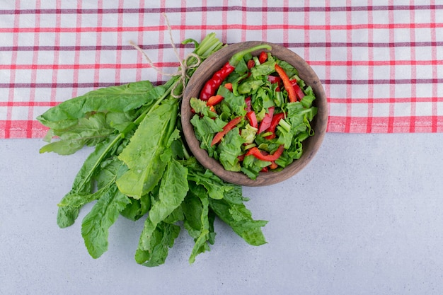 Fresh watercress leaves and a bowl of salad on marble background. high quality photo