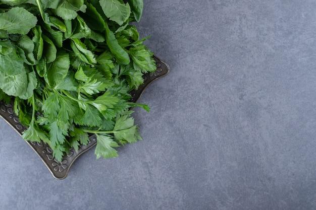 Crescione fresco su un vassoio, sulla superficie di marmo.