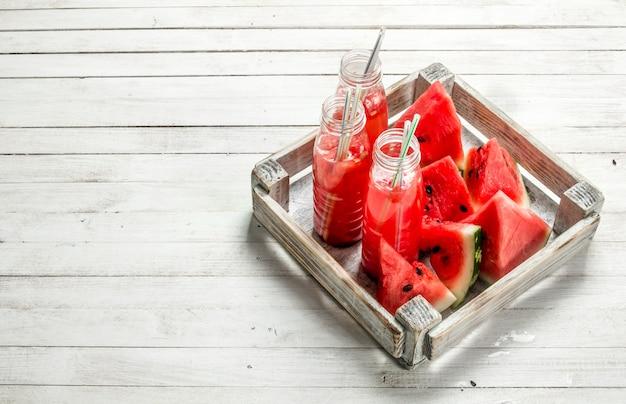 ボトルに入った新鮮なスイカジュース。白い木製のテーブルの上。
