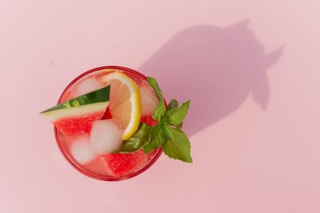 Свежий арбузный сок с мятой и льдом в стакане на розовом фоне. сладкий летний десерт, концепция здорового питания коктейля, вид сверху. лето. выборочный фокус.