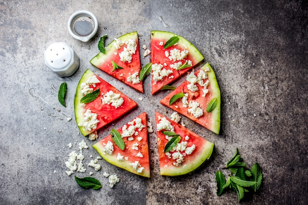 Fresh watermelon pizza salad with feta cheese, mint, salt and oil on stone