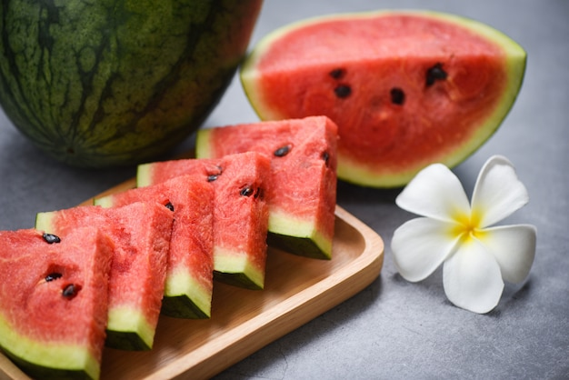Fresh watermelon slice and white flower on concrete