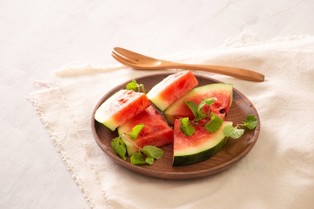 직물 표면에 나무 접시에 신선한 수박 슬라이스