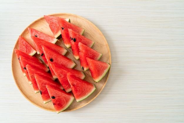 Свежий арбуз нарезанный на деревянной тарелке