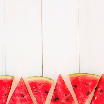 Fresh watermelon slices in triangular shape on wooden plank