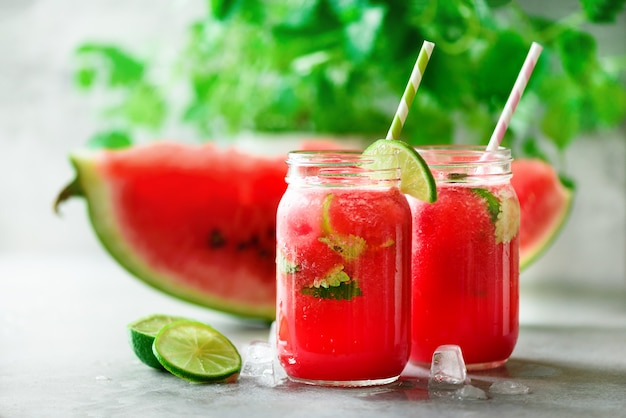Fresh watermelon smoothie in glass jar on light background