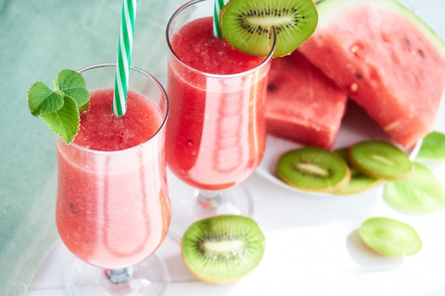 Fresh watermelon smoothie with kiwi and mint on a white table