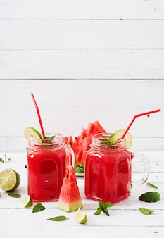 Fresh watermelon smoothies with lime and mint on white wooden table