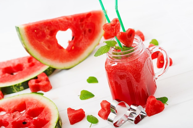 Fresh watermelon smoothies with mint on white wooden table.