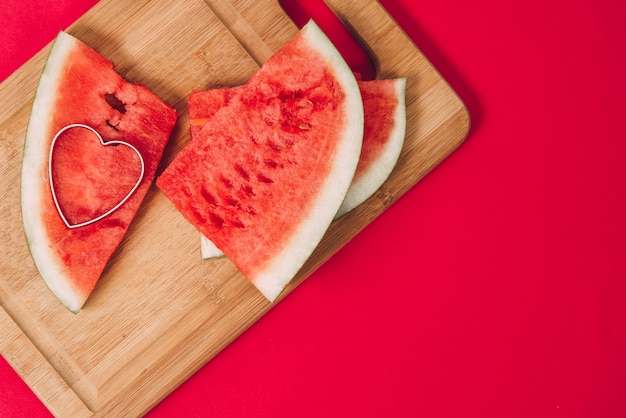 Fresh watermelon on a wooden board and heart shape on a red background. valentine's day card