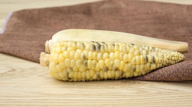 Fresh waxy corn on a wooden table.