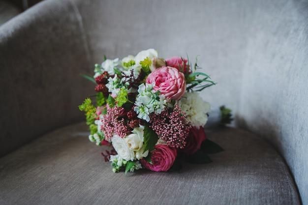 Свежий свадебный букет на стуле. подготовка к свадьбе