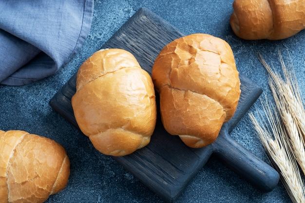 신선한 밀 빵 롤. 핫도그 또는 햄버거 롤. 어두운 배경 복사 공간.