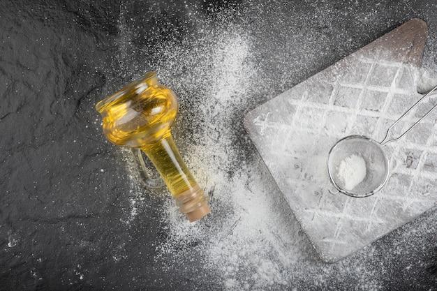 Pavimento di grano fresco versato su una tavola di legno con un bicchiere d'olio