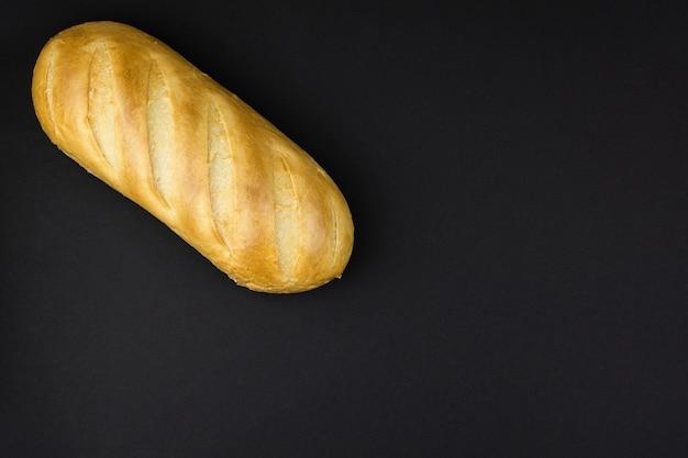 Свежая пшеничная буханка белого хлеба на черном фоне