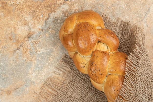 Pane bianco fresco su tela di sacco sulla superficie in marmo.