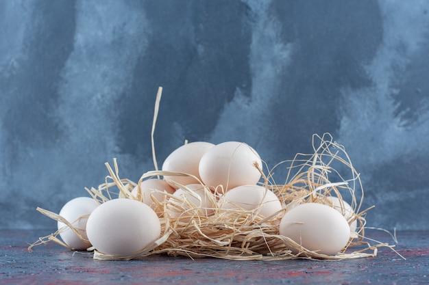 Uova di gallina bianche e marroni fresche con fieno.