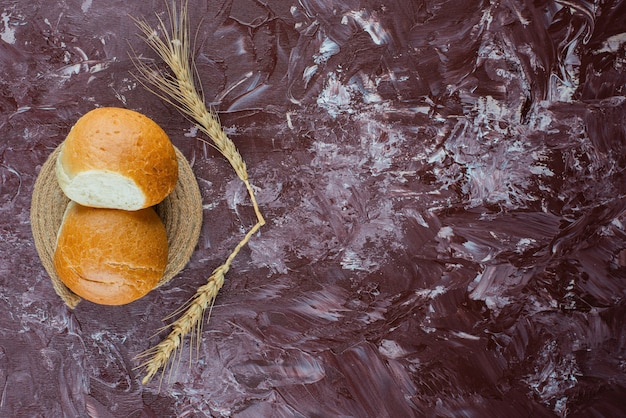 Fresh white buns with wheat ears on a light background .