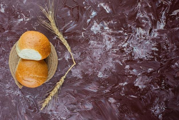 Свежие белые булочки с колосьями пшеницы на светлом фоне.