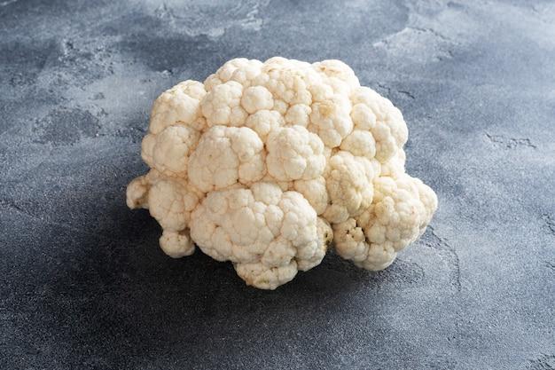 Fresh white cauliflower on a grey concrete background