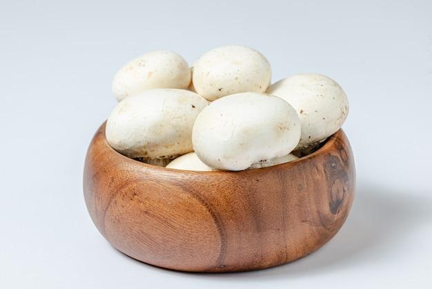 Fresh white champignons in brown bowl on white background.