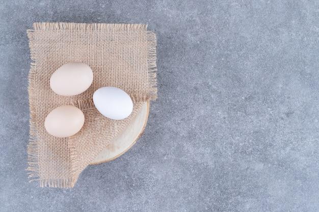 Uova di gallina bianche fresche su una superficie di marmo