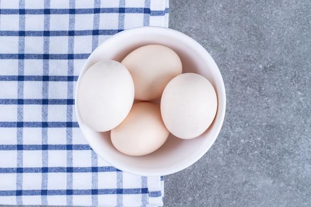 Uova di gallina bianche fresche su un piatto bianco