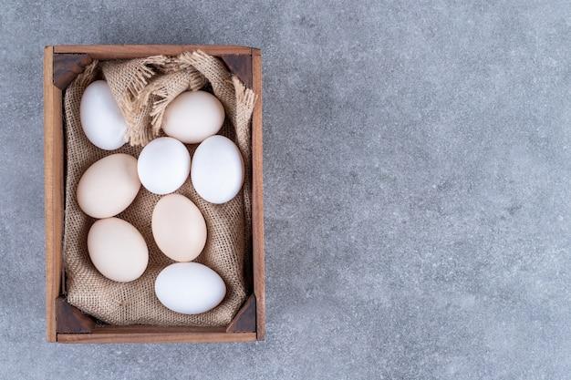 Uova di gallina bianche fresche su un canestro di legno
