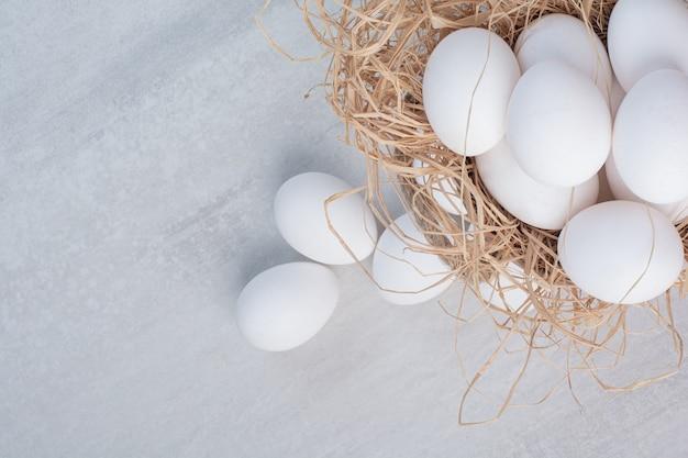 Uova fresche bianche su sfondo di marmo.