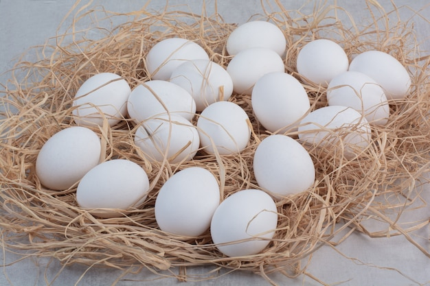 Свежие белые яйца на мраморном фоне.