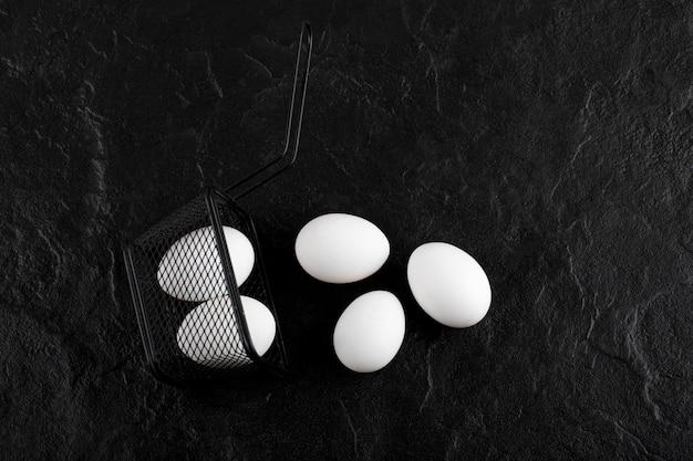 黒い容器から出た新鮮な白い卵。