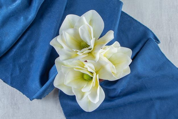 Fiori bianchi freschi in un bicchiere su un pezzo di tessuto, sul tavolo bianco.