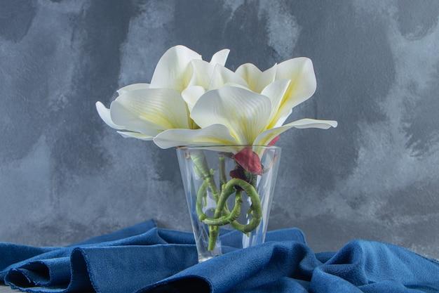 흰색 바탕에 천 조각에 유리에 신선한 흰색 꽃. 고품질 사진