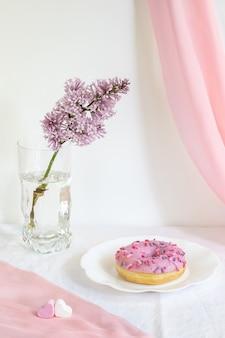 Fresh white glazed donut on curly plate on white background