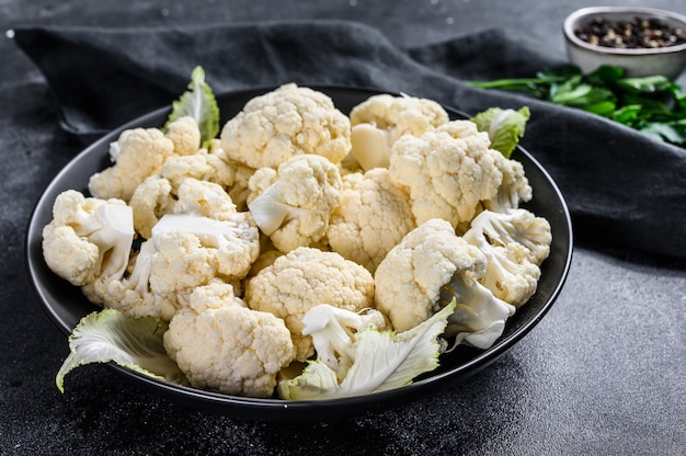 Fresh white heads cleaned cauliflower in a bowl. black background. top view